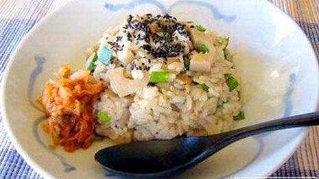 キムチを添えてゴマをふりかける「レンコンの炊き込みご飯」