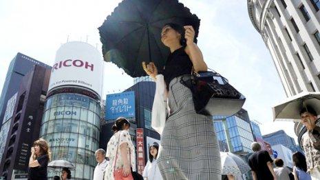 強い日差しが照りつける中、東京・銀座を行き交う人たち