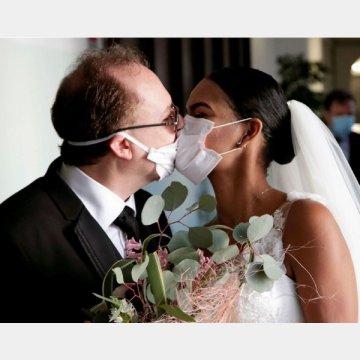 イタリア南部ナポリで、招待客なしで行われた結婚式でマスクをしたままキスする新郎新婦