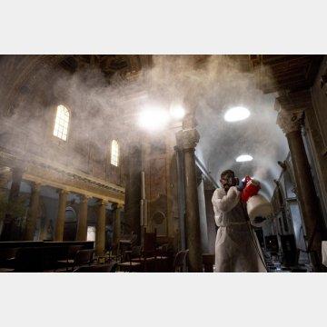 すべての国が現在も新型コロナウイルスと闘っている(ローマの聖堂で消毒液をまく男性)/