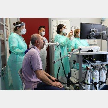 新型コロナウイルスに感染し退院後も体調不良が続く人を対象にしたリハビリ施設で検査を受ける元患者(手前)=イタリア・ジェノバ