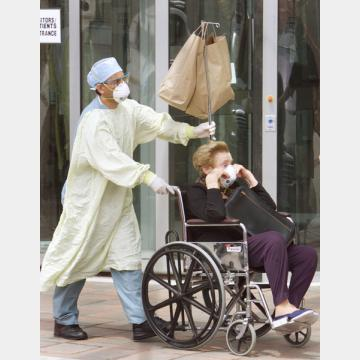 2003年、カナダでSARSが流行し273人が感染した(退院するSARS高齢患者を、彼女の車まで付き添う防護服の病院従業員)