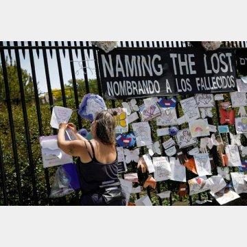 墓地の前で新型コロナに感染し亡くなった犠牲者の名前を記す女性