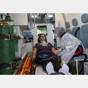 救急車内で新型コロナウイルス陽性反応を示した患者の治療にあたる救急医療チームの看護師