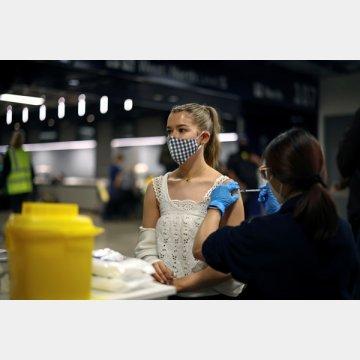 集団ワクチン接種センターでファイザー製ワクチンを接種される若者(ロンドン=トッテナム・ホットスパースタジアム)
